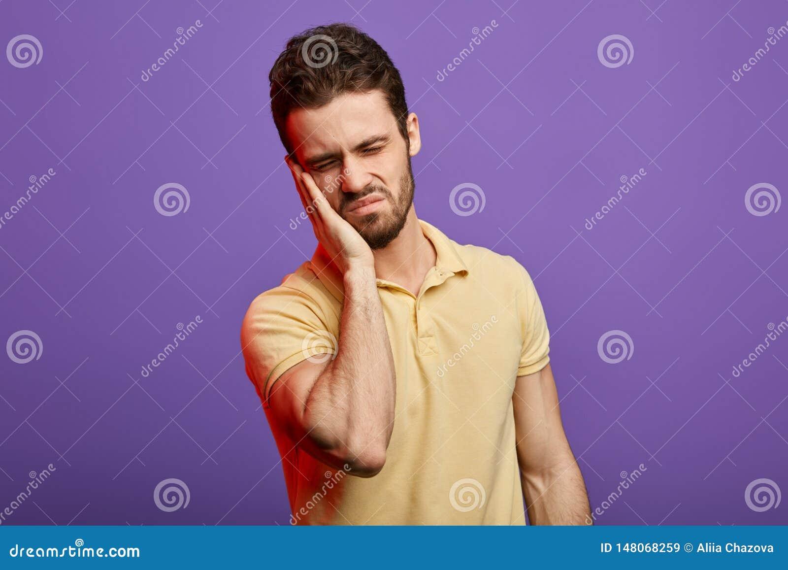 Emotionele knappe mens die pijn voelen, die zijn wang houden, die aan tandpijn lijden