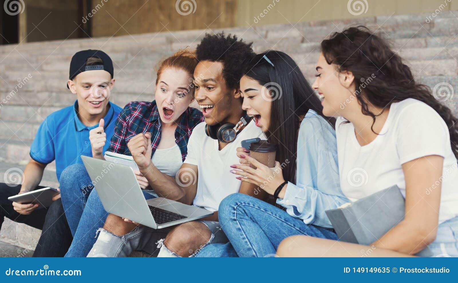 Emotionele Tienerstudenten kijken die die in Laptop worden opgewekt