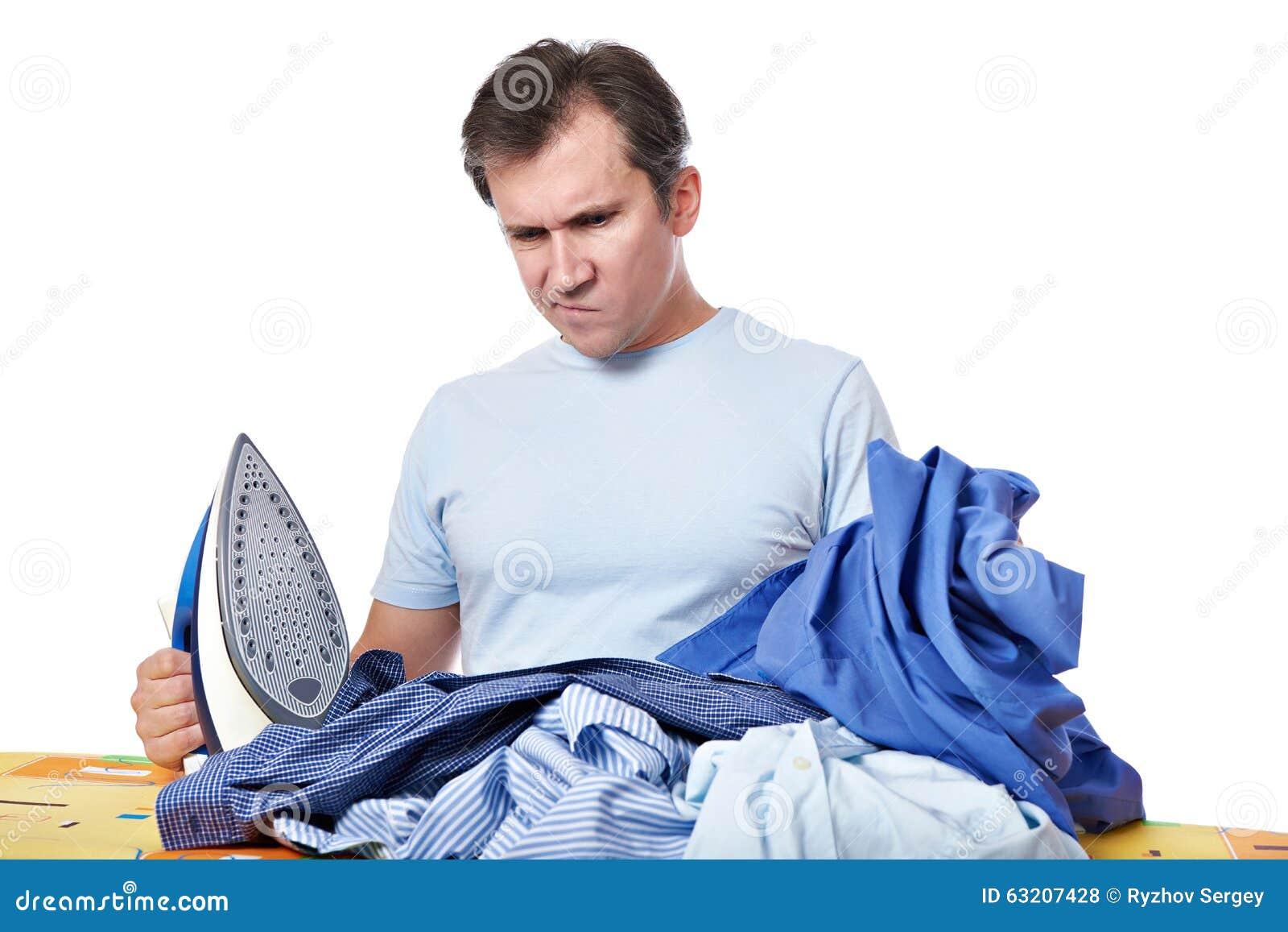 Emotionell man med en hög av tvätterit, innan isolerat att stryka