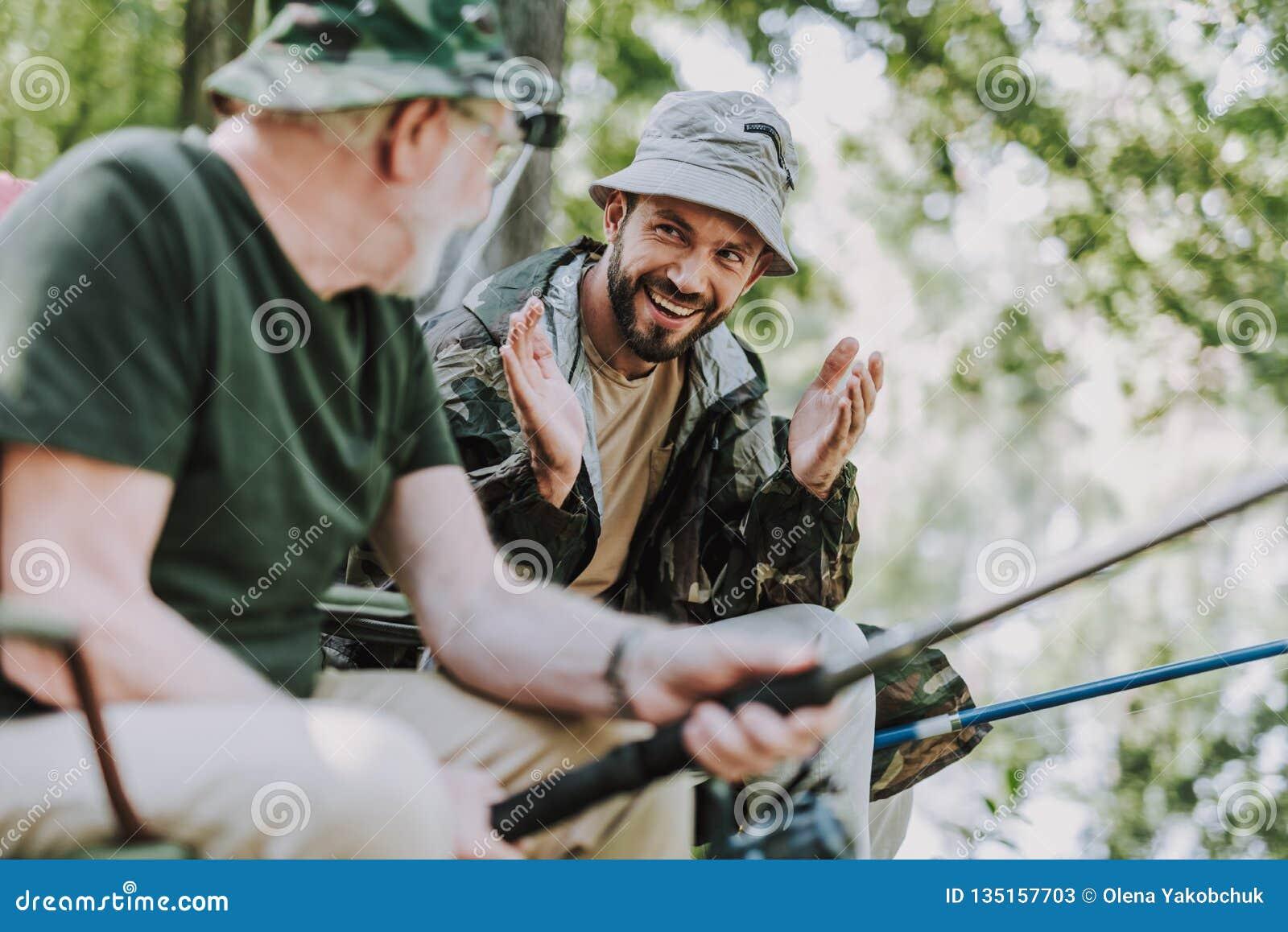 Emotionell skäggig man som fiskar med hans äldre fader