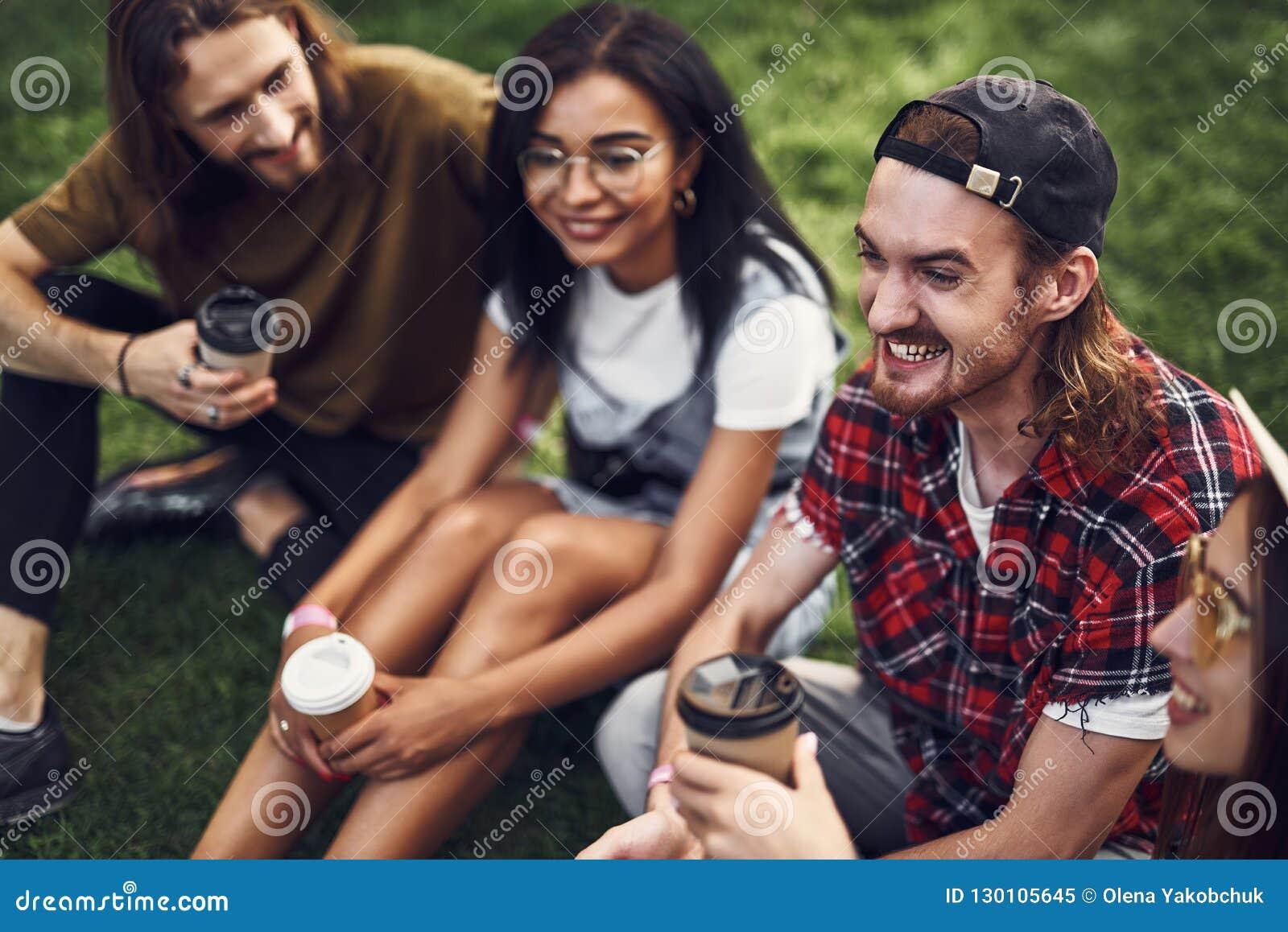 Emotionella vänner som sitter på gräset och ser lyckliga