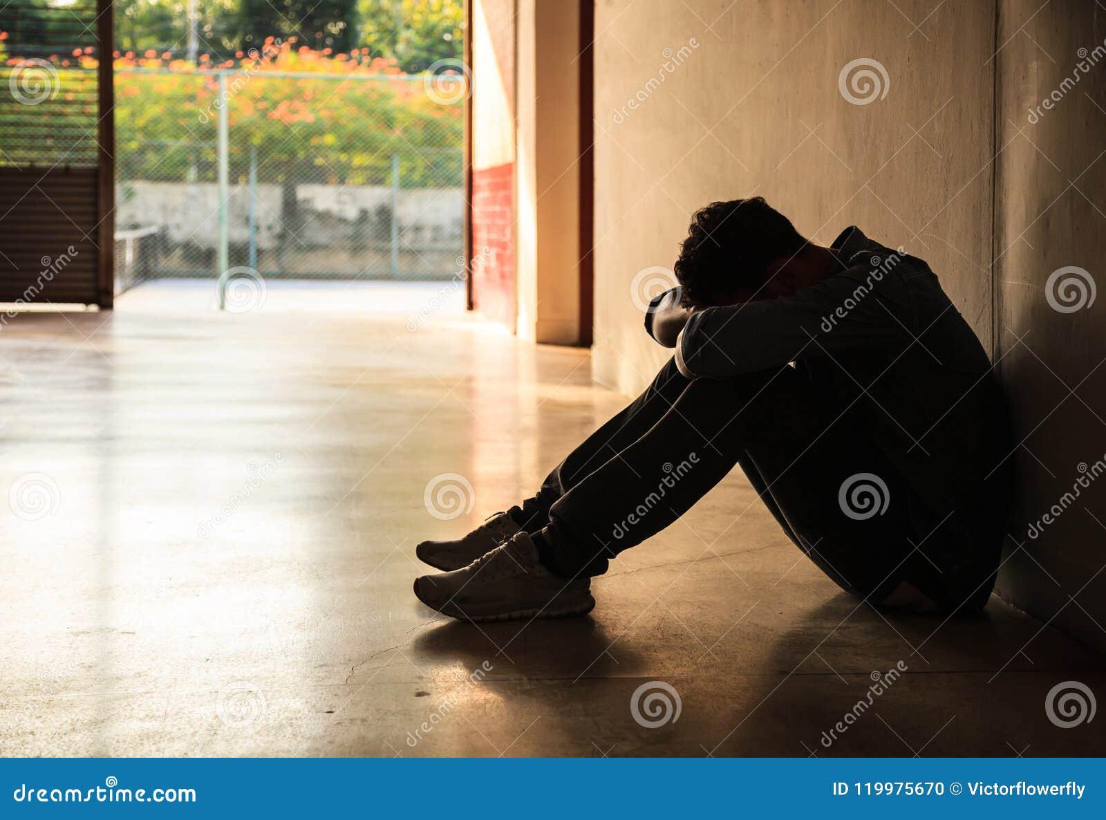 Emotionellt ögonblick: man det hållande head bottenläget för sammanträde på knä, den stressade ledsna unga mannen som har mentala