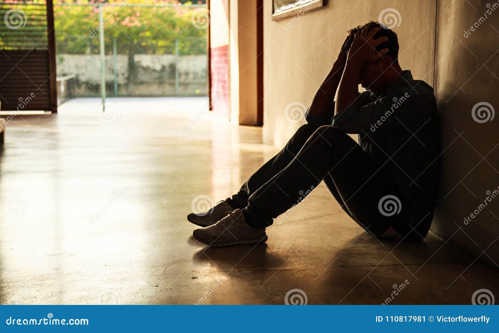 Emotionellt ögonblick: man det hållande huvudet för sammanträde i händer, den stressade ledsna unga mannen som har mentala proble