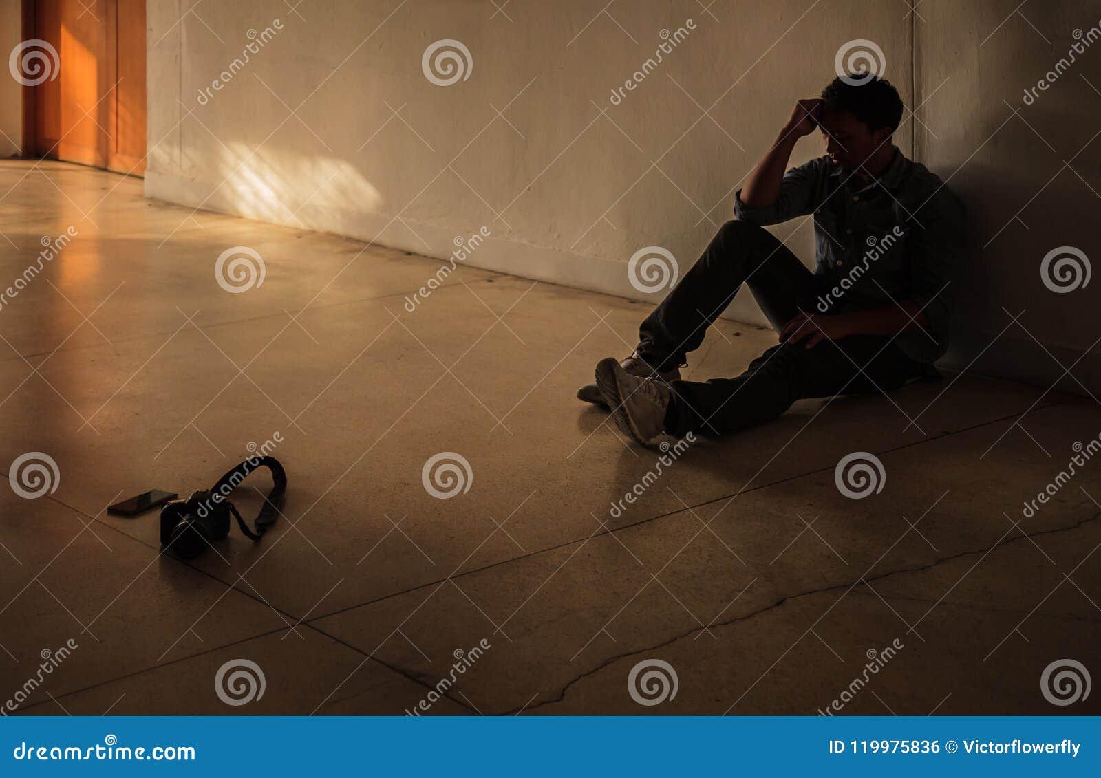Emotionellt ögonblick: man det hållande huvudet för sammanträde vid handen, den stressade ledsna unga mannen som har mentala prob
