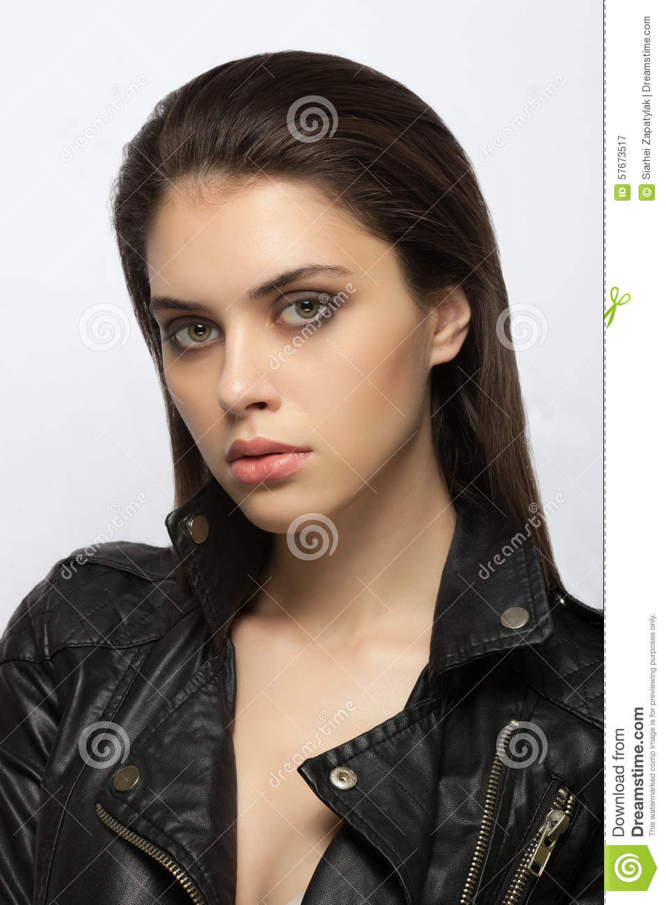 Emotive closeup portrait of a young attractive brunette woman posing for model tests in black leather jacket
