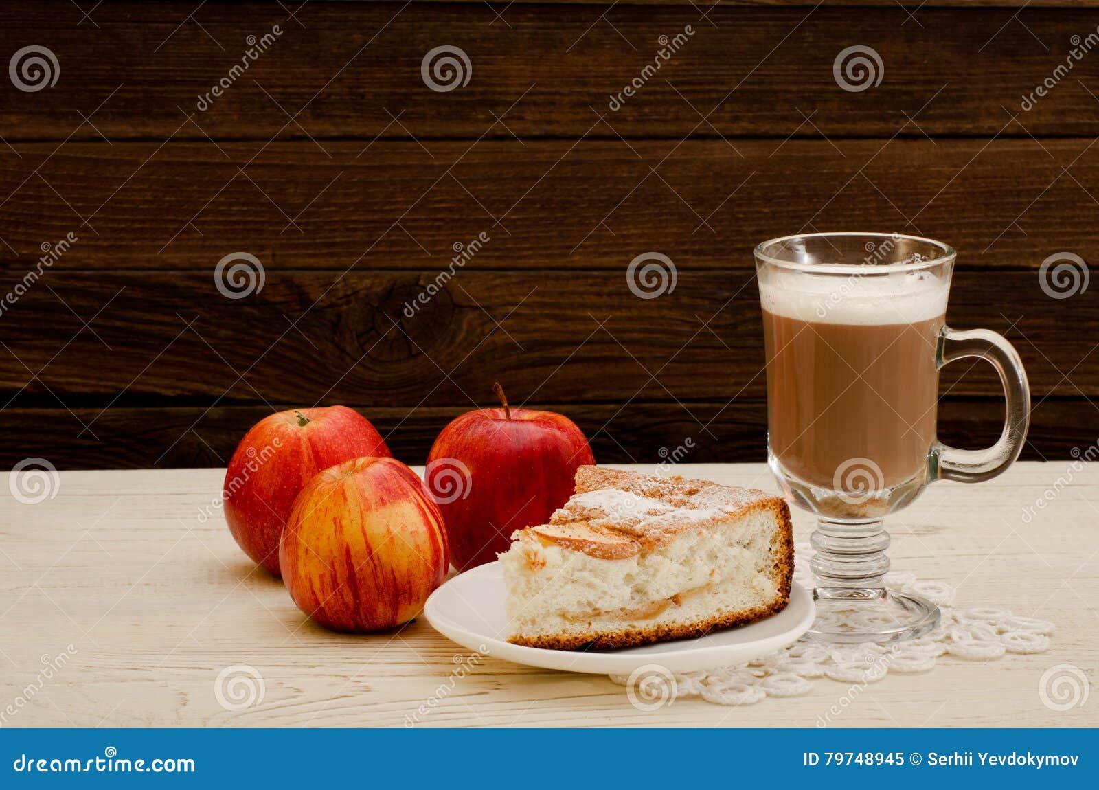Empanada de Apple, capuchino y manzanas maduras en un fondo de madera