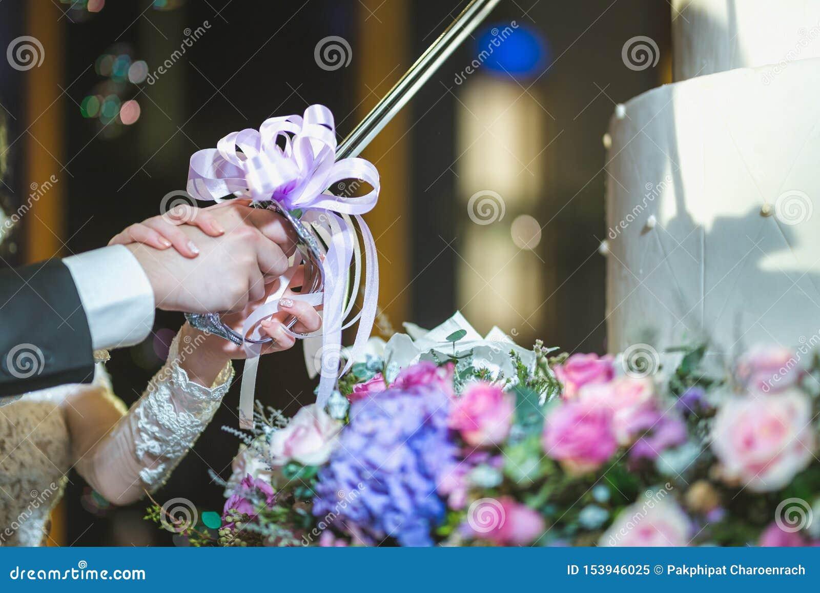 Empanada 8 de la boda novia magn?fica y novio elegante que cortan el pastel de bodas elegante con las flores en la recepci?n nupc