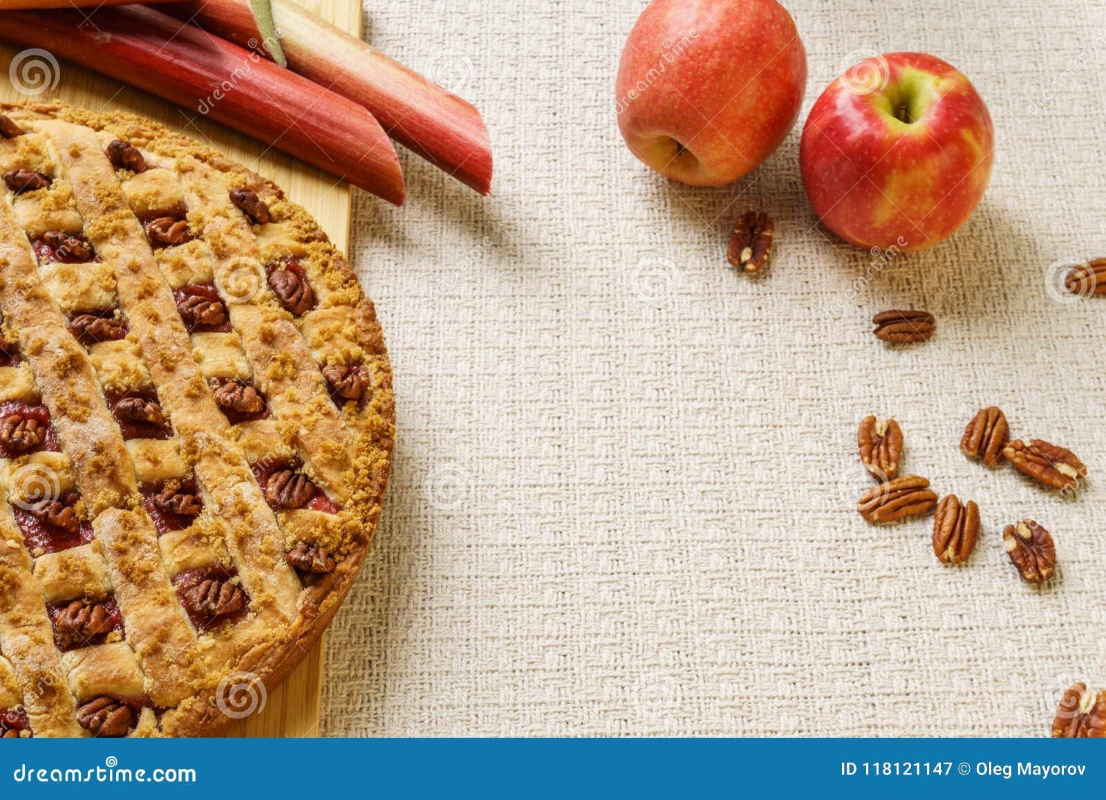 Empanada entera de la manzana y de ruibarbo con la pacana en una bandeja negra en una tabla