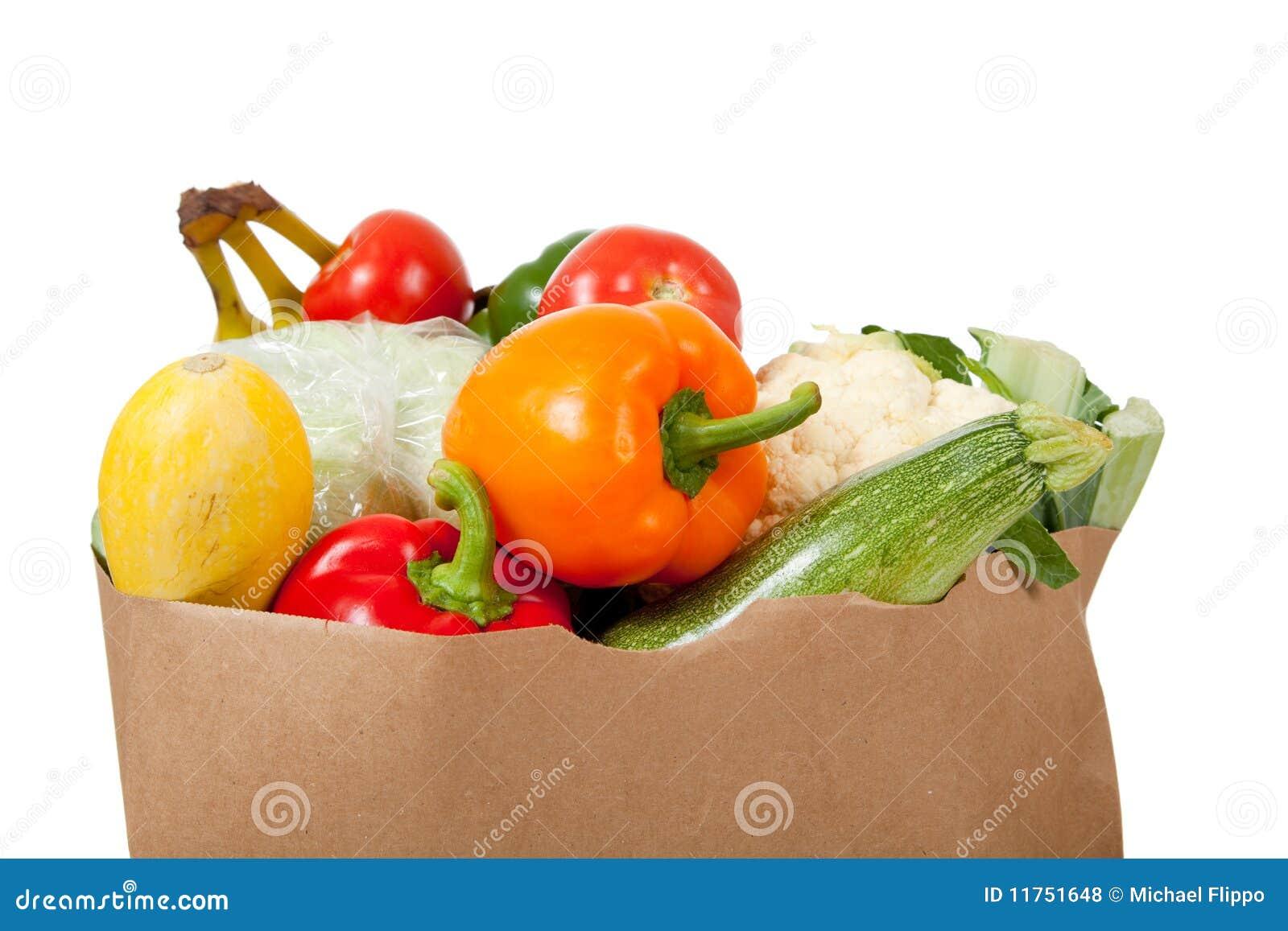 Empaquetez le sac à épicerie avec des légumes sur le blanc