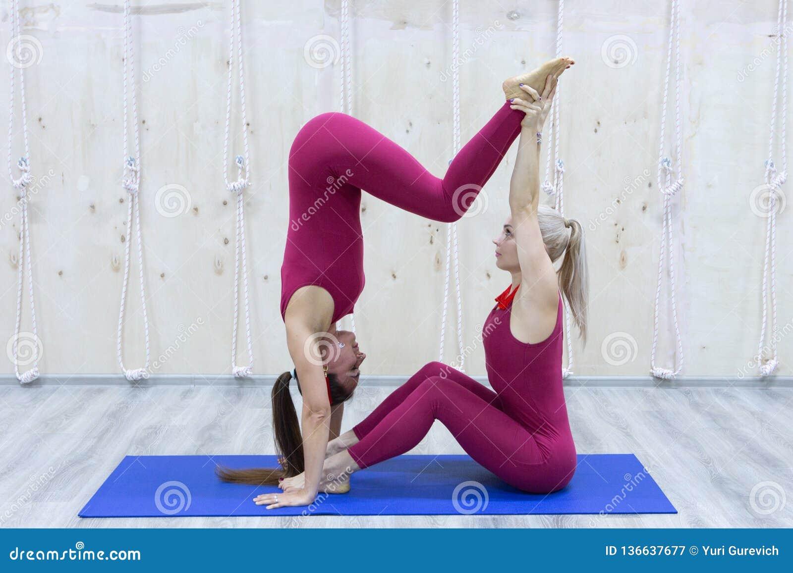 Emparelhe as mulheres desportivas da ioga que fazem o exercício no fundo à moda cinzento Pose da ioga dos pares
