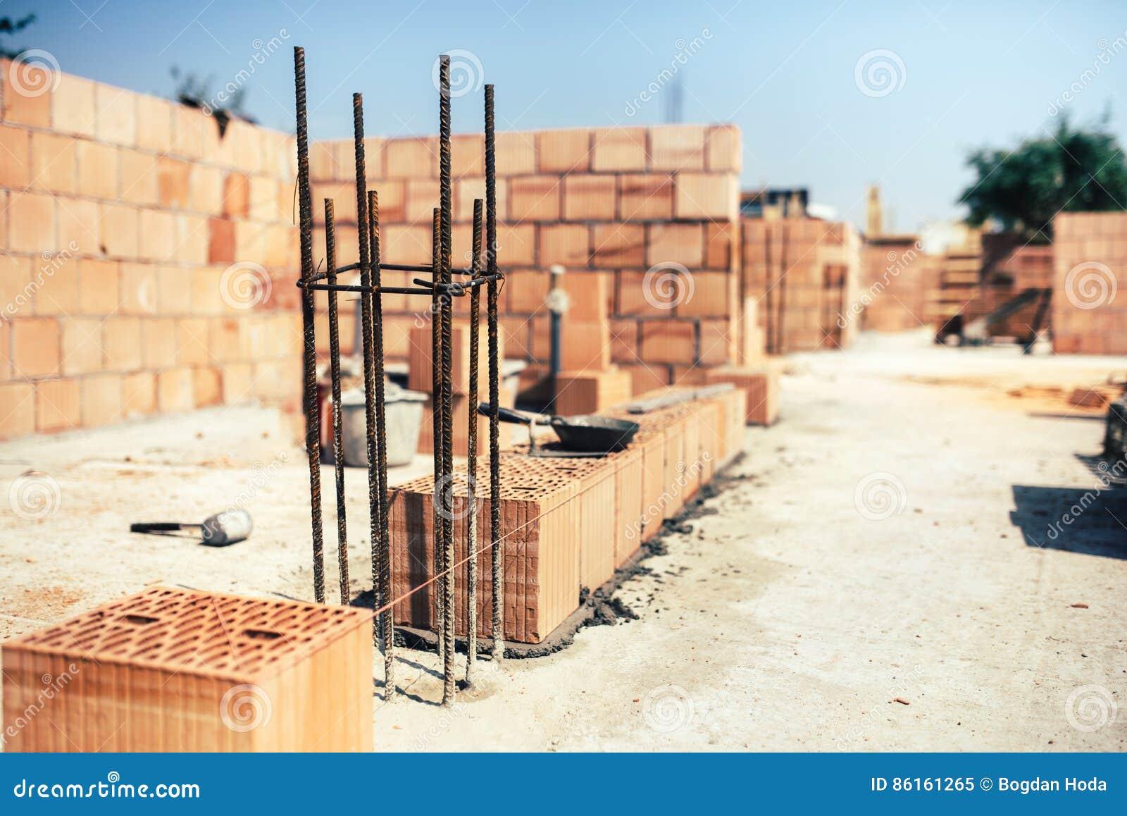 de la obra colocando ladrillos en el cemento mientras que construye las paredes exteriores