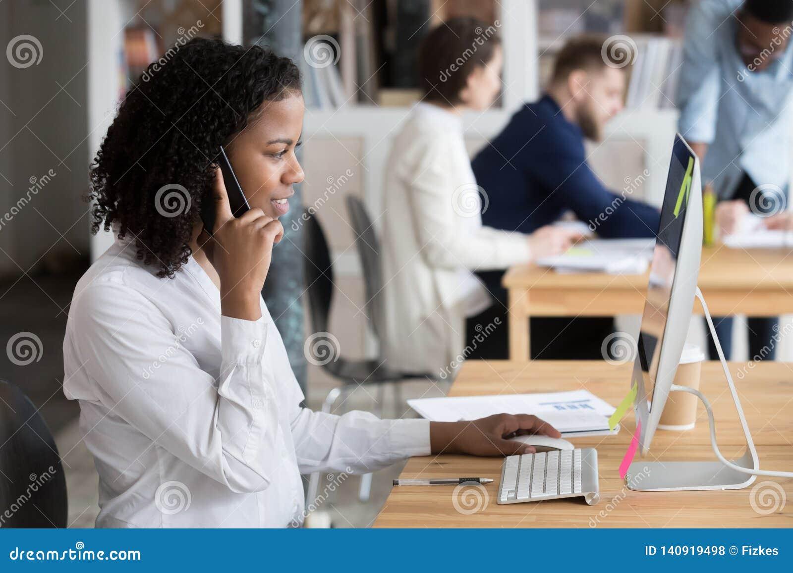 Empleado africano negro que habla en el teléfono que se sienta en el escritorio de oficina
