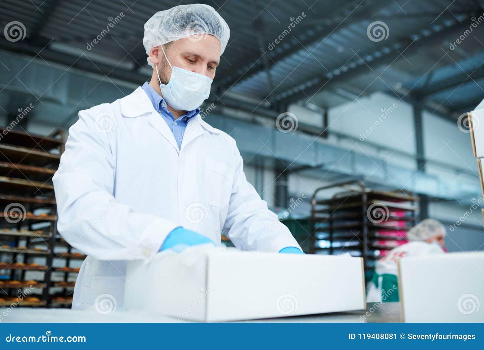 Empleado de la fábrica de la confitería que prepara el paquete