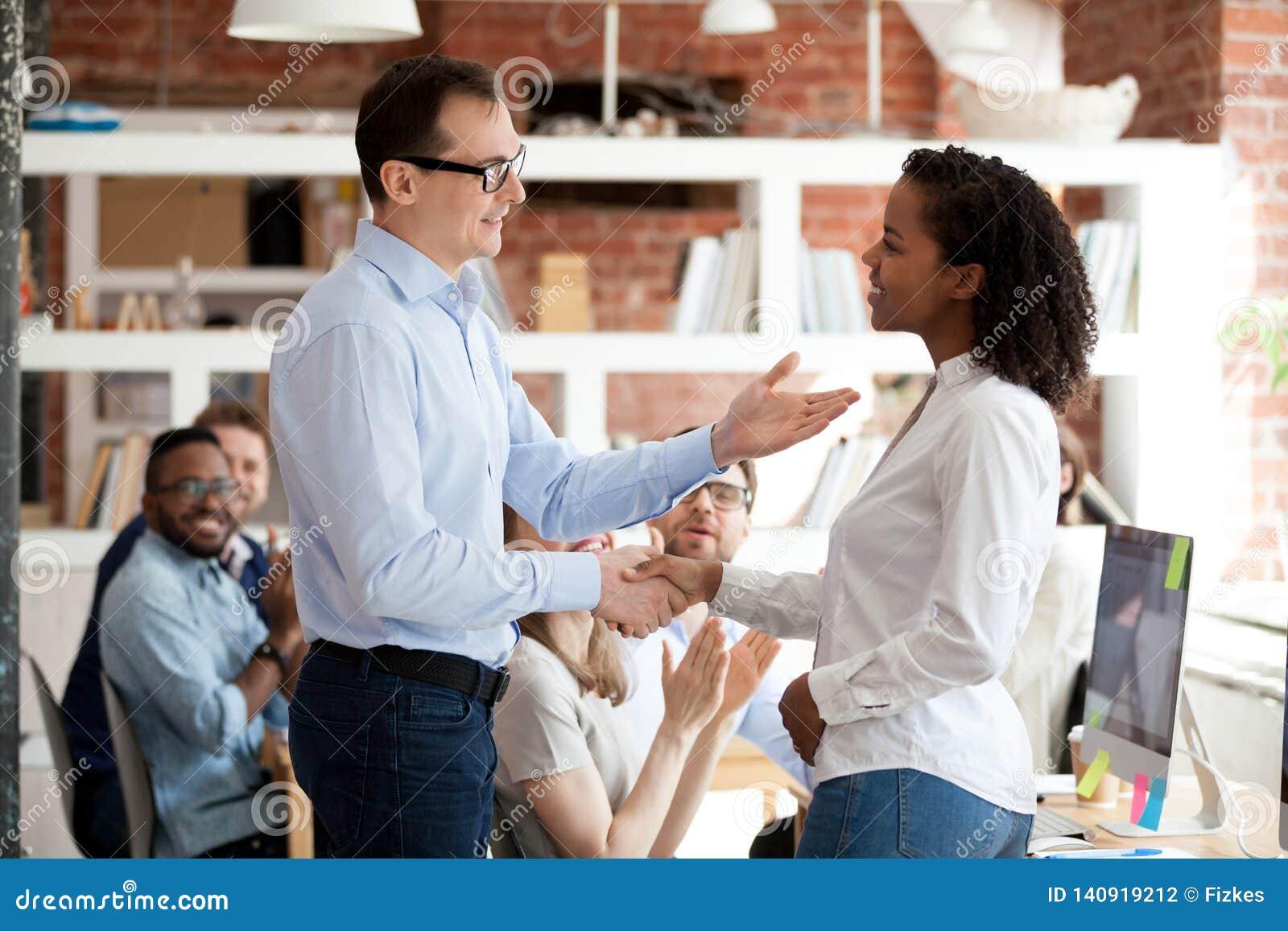 Empleado que consigue alabanza del jefe mientras que colegas que aplauden