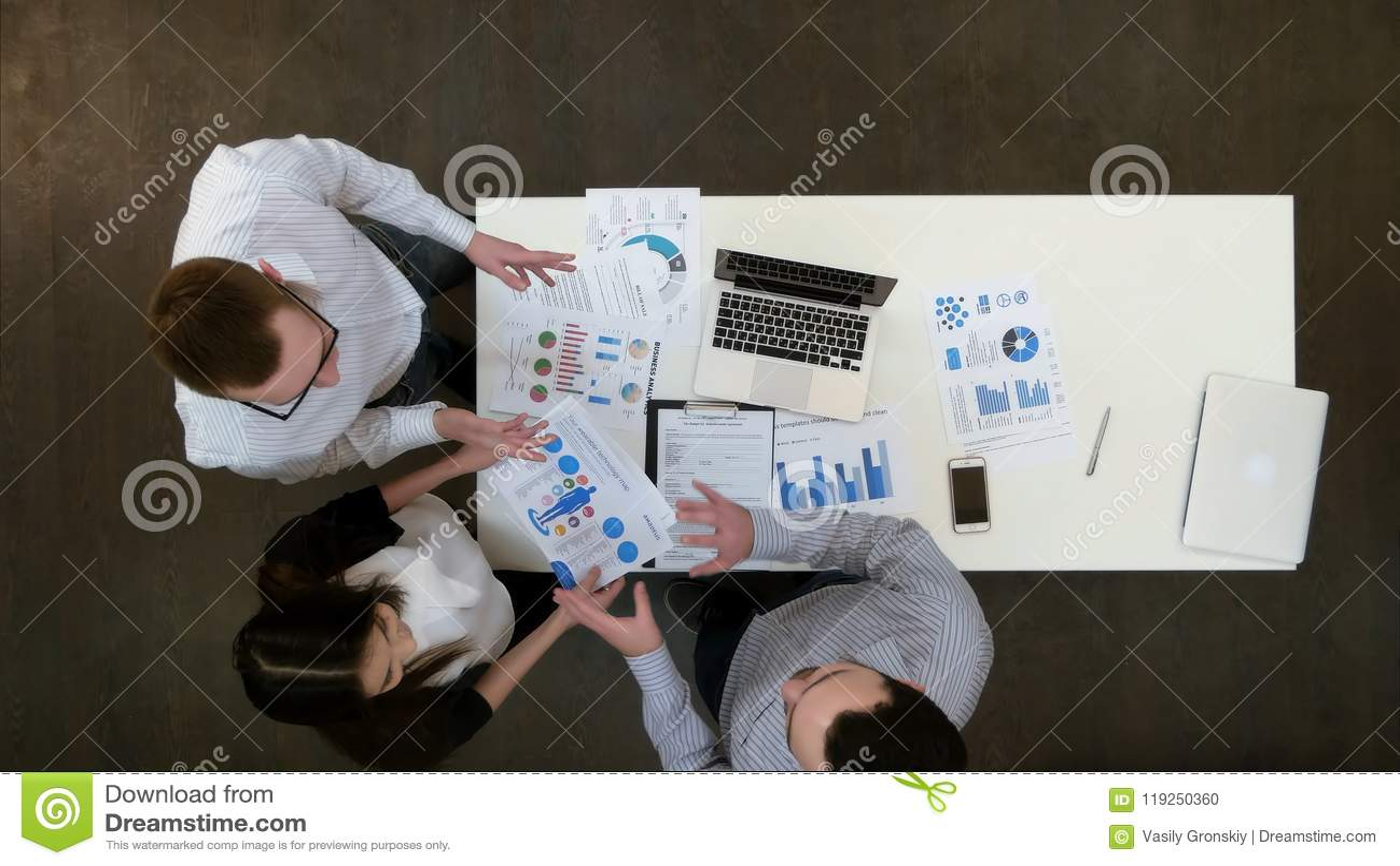 Empleados de oficina jovenes positivos que discuten los papeles en la reunión de negocios