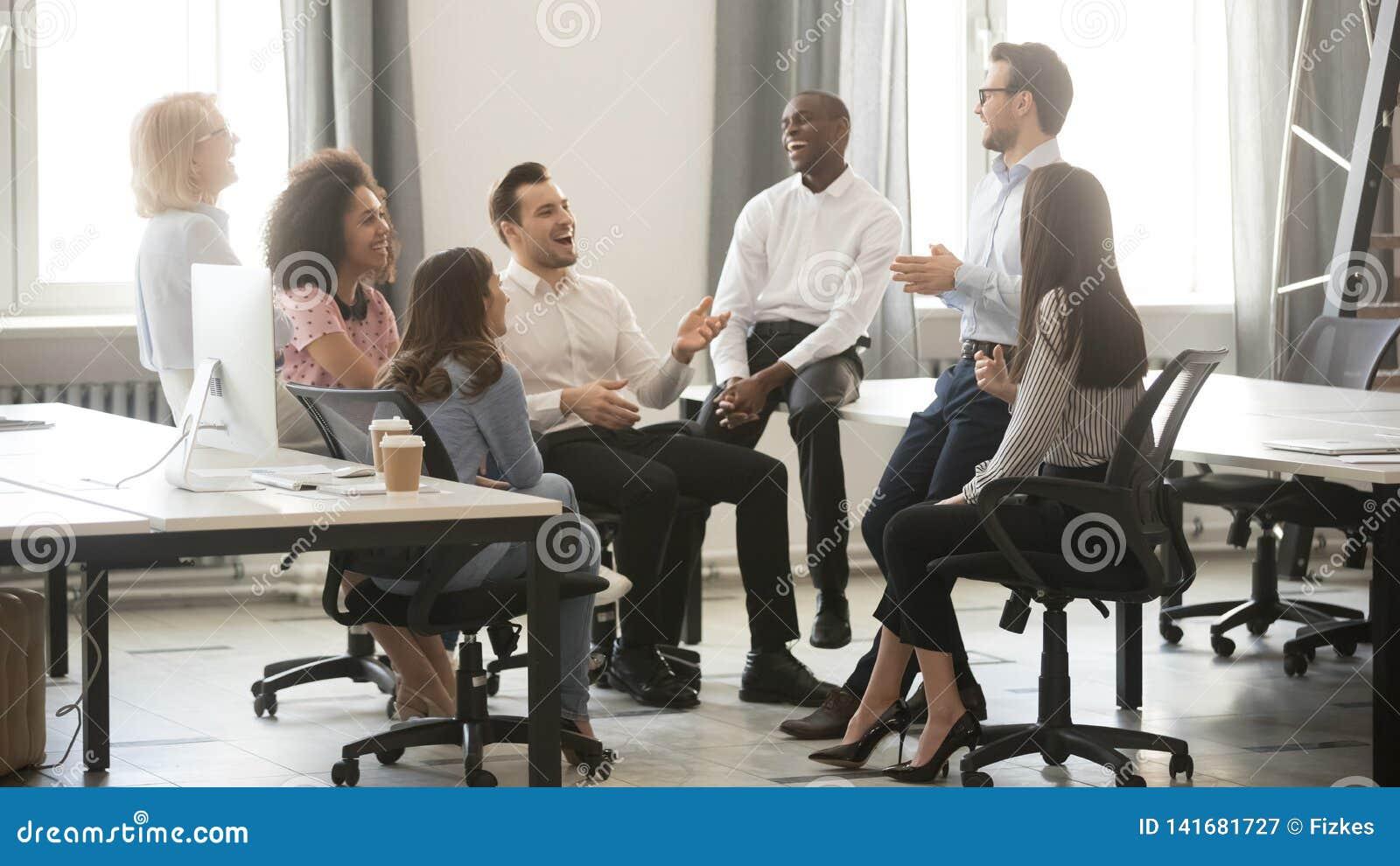 Empleados diversos felices del equipo del negocio que se divierten en la reunión corporativa