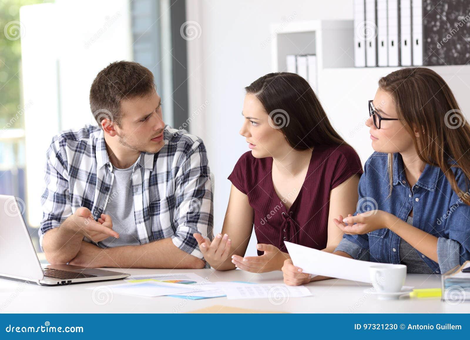 Empleados que tienen una conversación del trabajo en la oficina