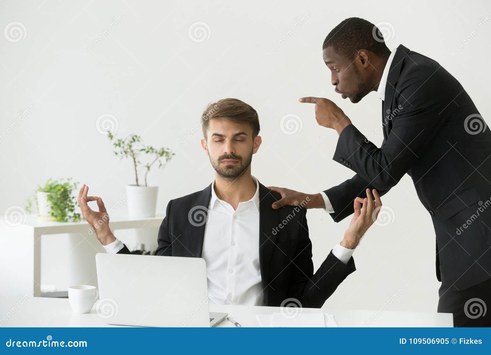 Employé caucasien méditant sur le lieu de travail ignorant le patron fâché s