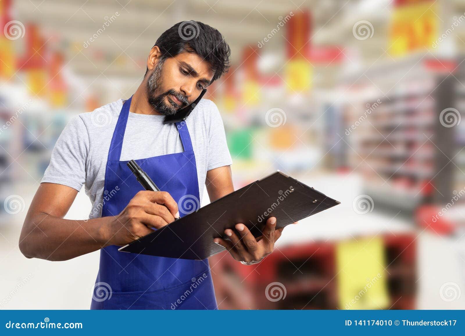 Employé d hypermarché parlant au téléphone et prenant des notes