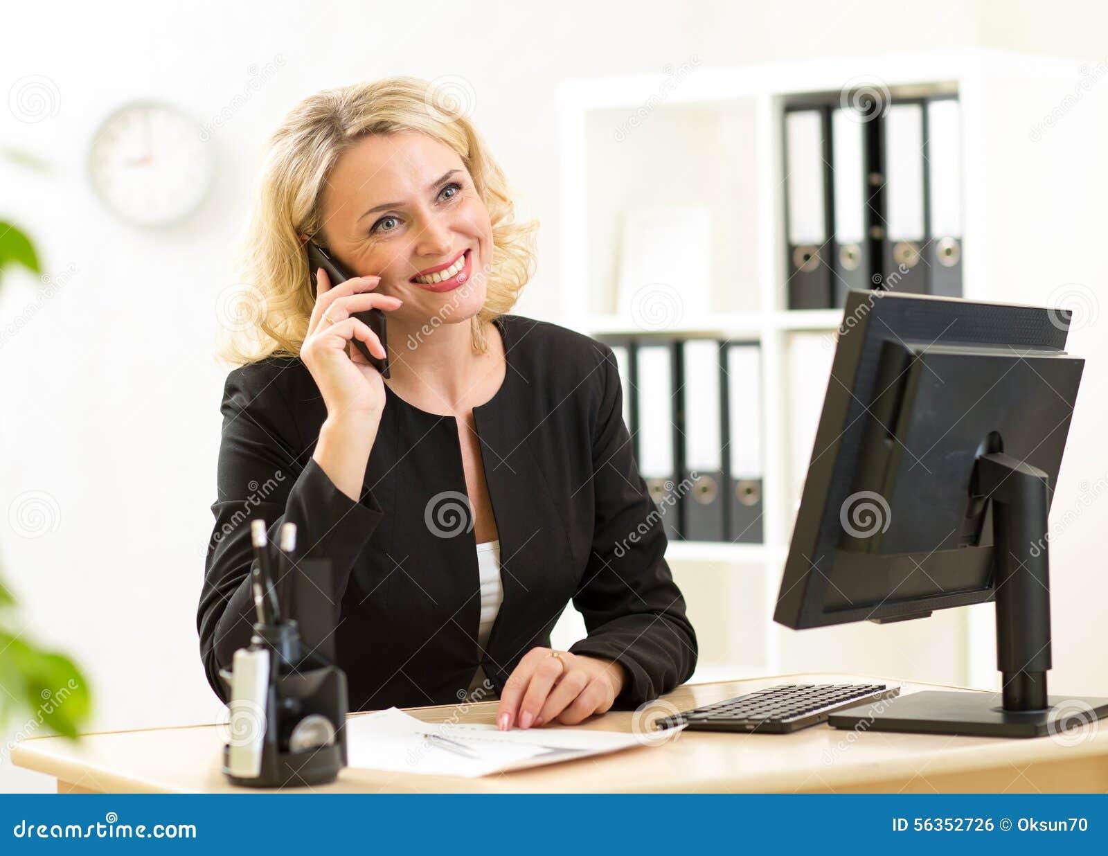 Employé de bureau d une cinquantaine d années mignon parlant au téléphone portable dans le bureau