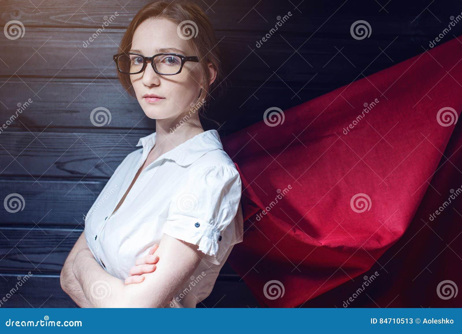 Employé de bureau de superwoman se tenant dans un costume et un manteau rouge