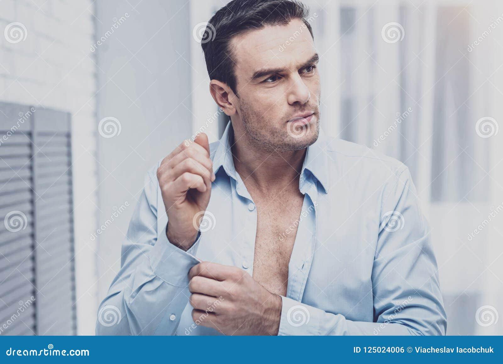 Employé de bureau sûr mettant sur une chemise