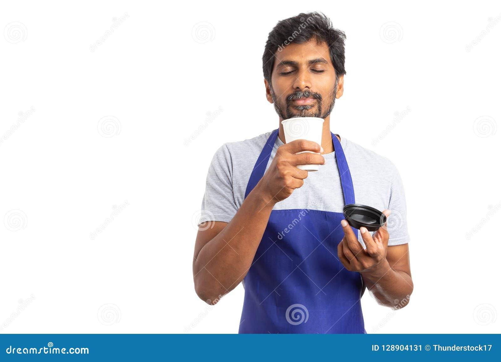 Employé indien sentant la boisson chaude pendant la pause-café