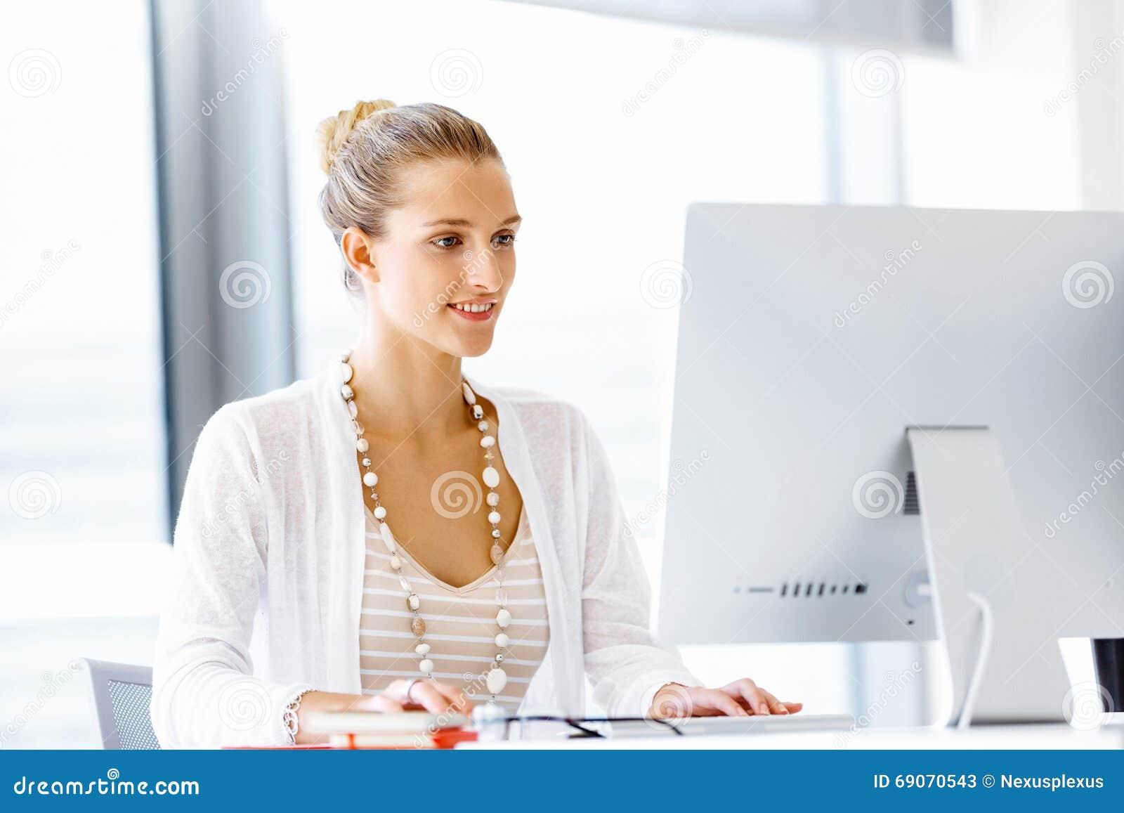employ de bureau attirant s 39 asseyant au bureau photo stock image 69070543. Black Bedroom Furniture Sets. Home Design Ideas
