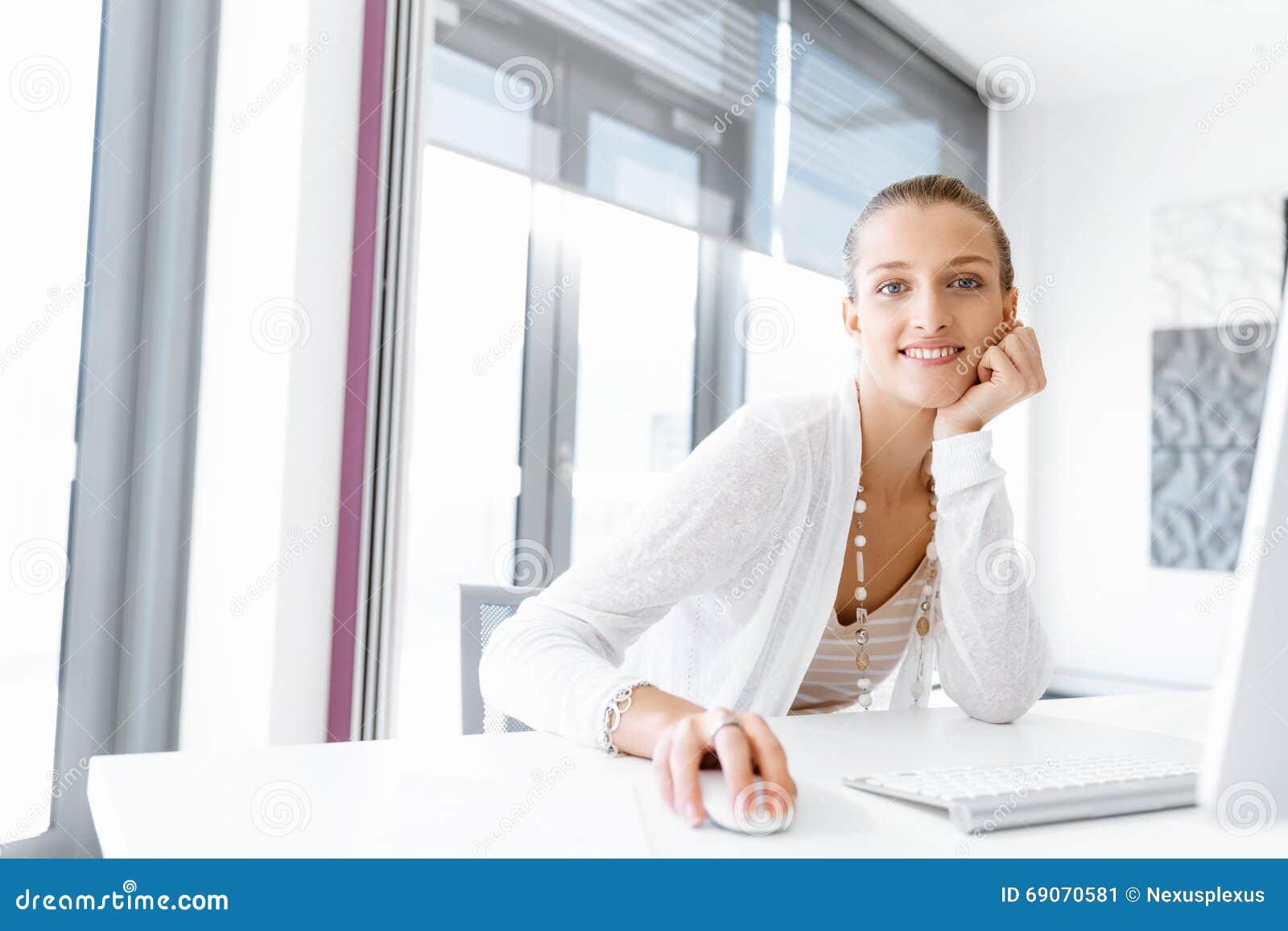 employ de bureau attirant s 39 asseyant au bureau photo stock image 69070581. Black Bedroom Furniture Sets. Home Design Ideas