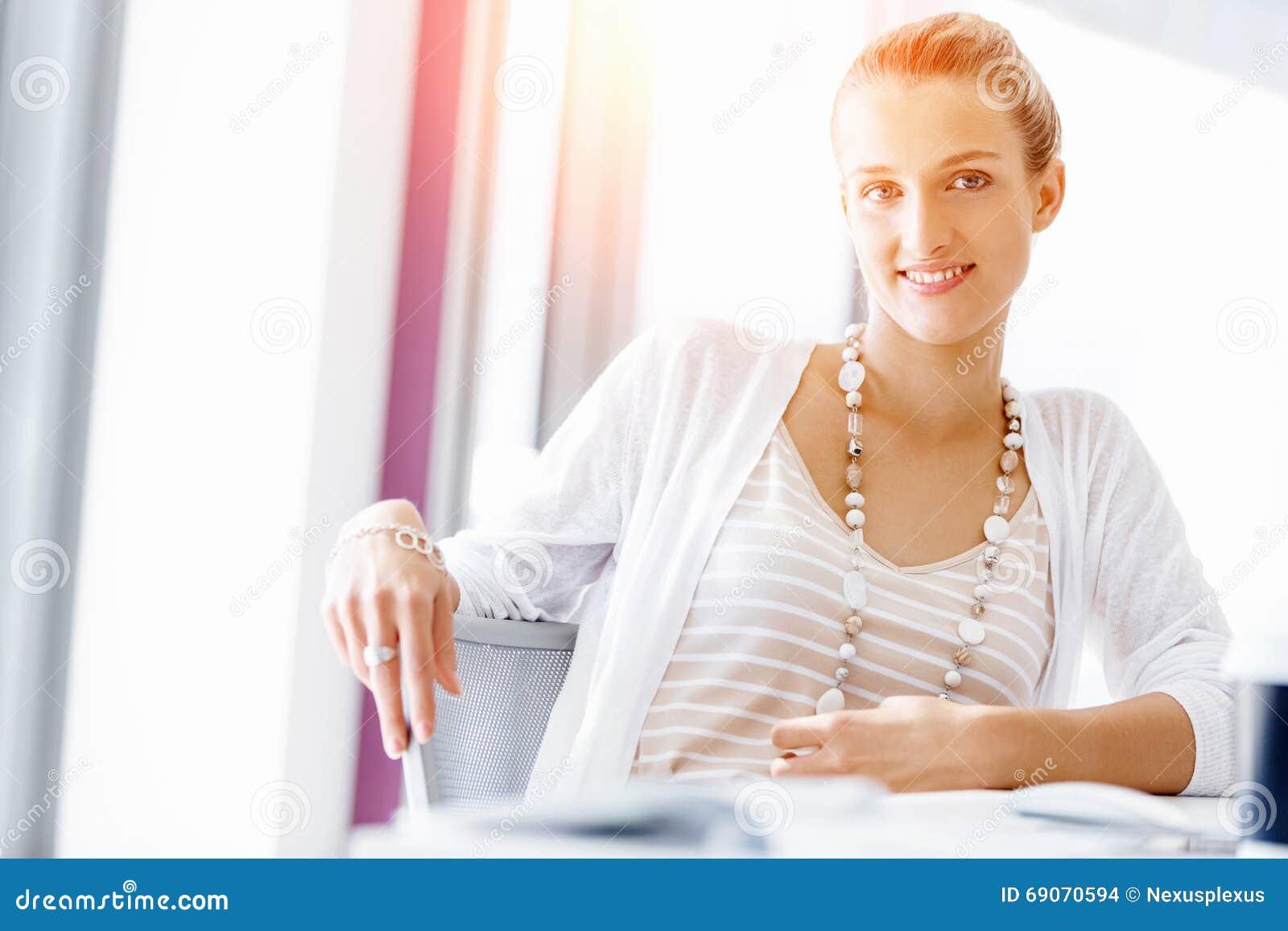 employ de bureau attirant s 39 asseyant au bureau photo stock image 69070594. Black Bedroom Furniture Sets. Home Design Ideas