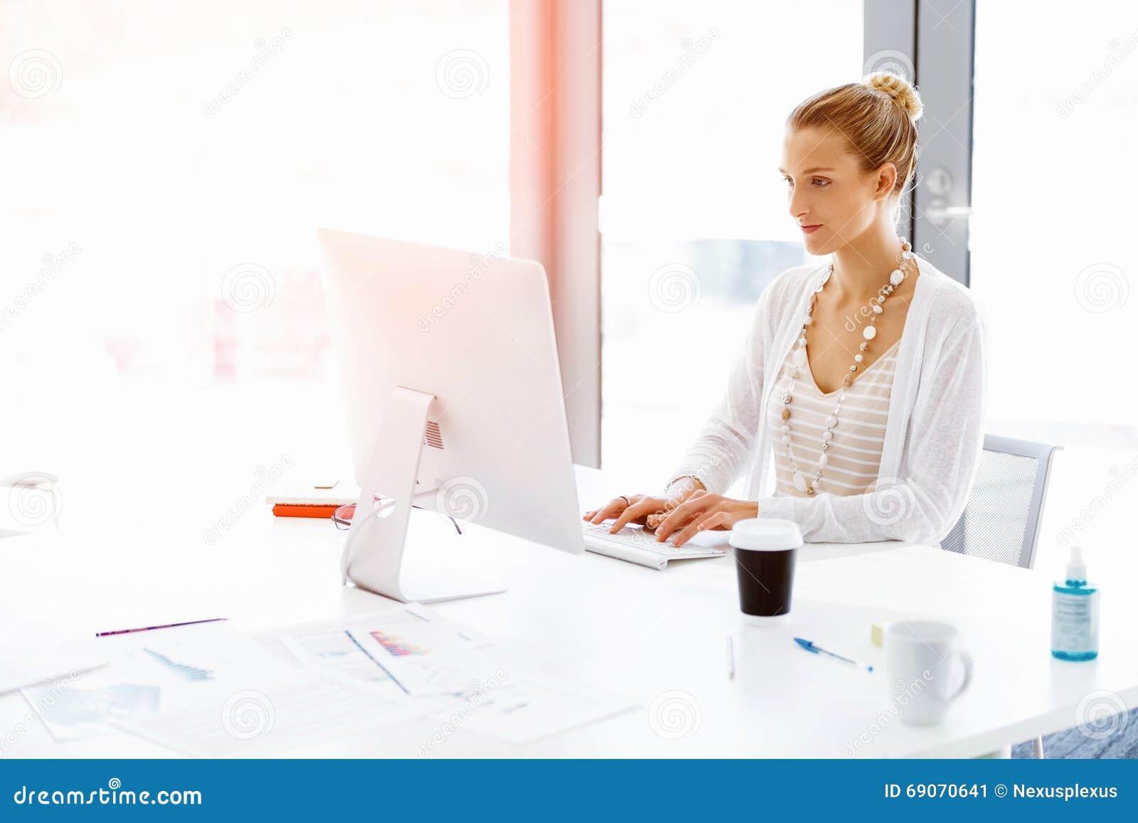 employ de bureau attirant s 39 asseyant au bureau photo stock image 69070641. Black Bedroom Furniture Sets. Home Design Ideas