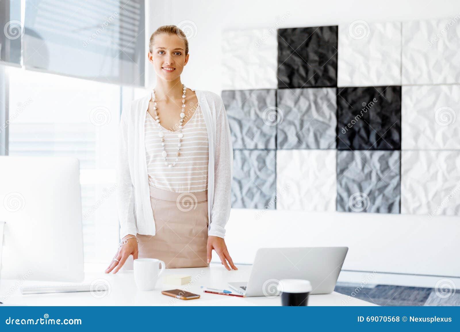 employ de bureau attirant se tenant c t de la fen tre photo stock image 69070568. Black Bedroom Furniture Sets. Home Design Ideas