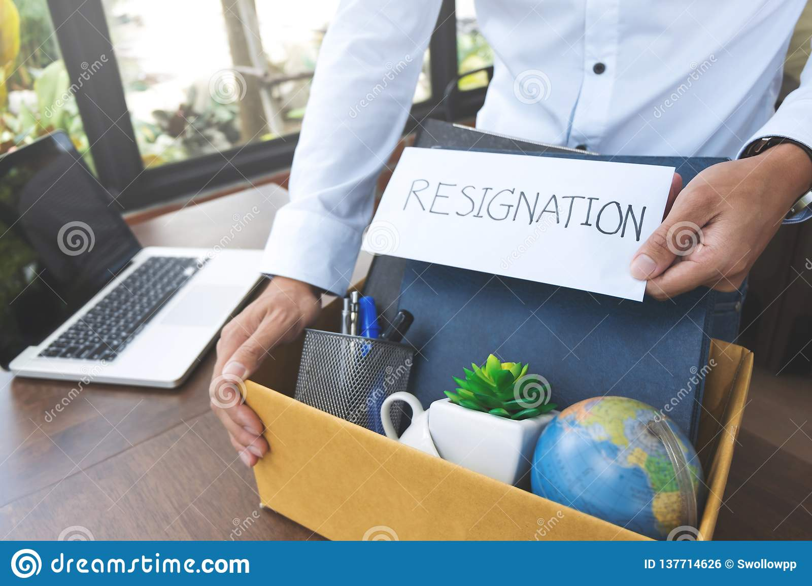 Employee holding resignation letter and Packing a Box To Leave The Office