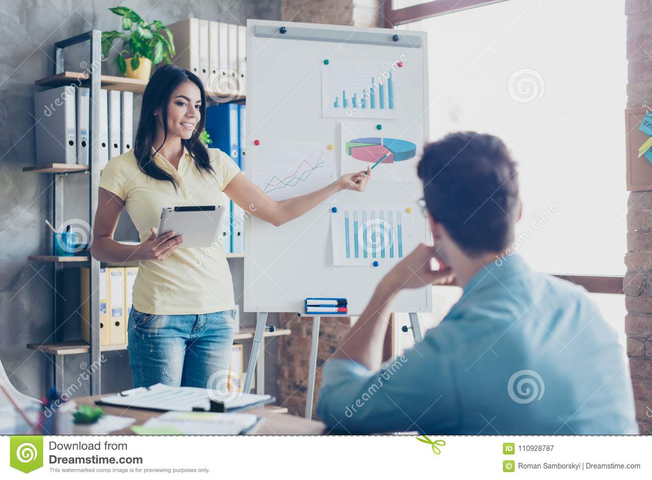 Employee making monthly report to her employer using modern gadget and flip board in office