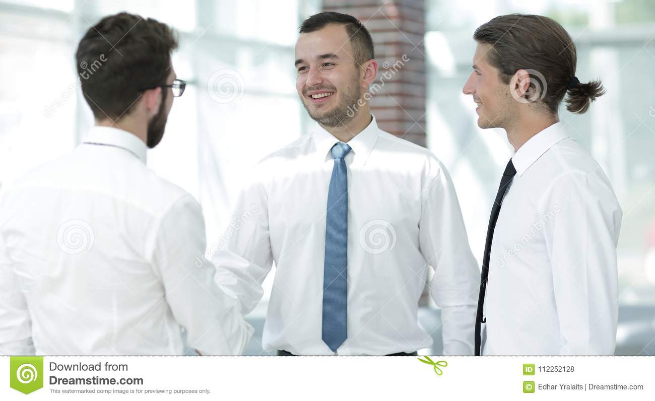 Employees greet each other by shaking hands stock photo image of employees greet each other by shaking hands standing in the office m4hsunfo