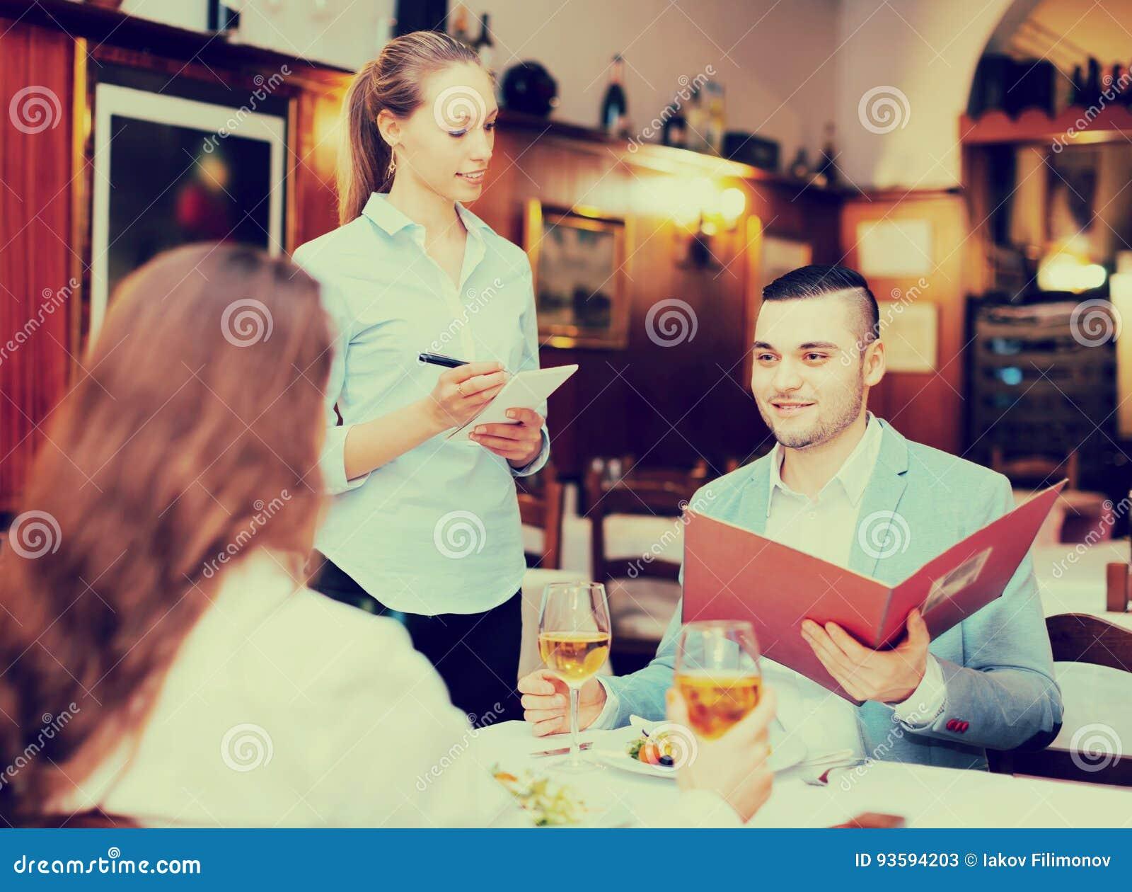 Empregada de mesa e convidados no café