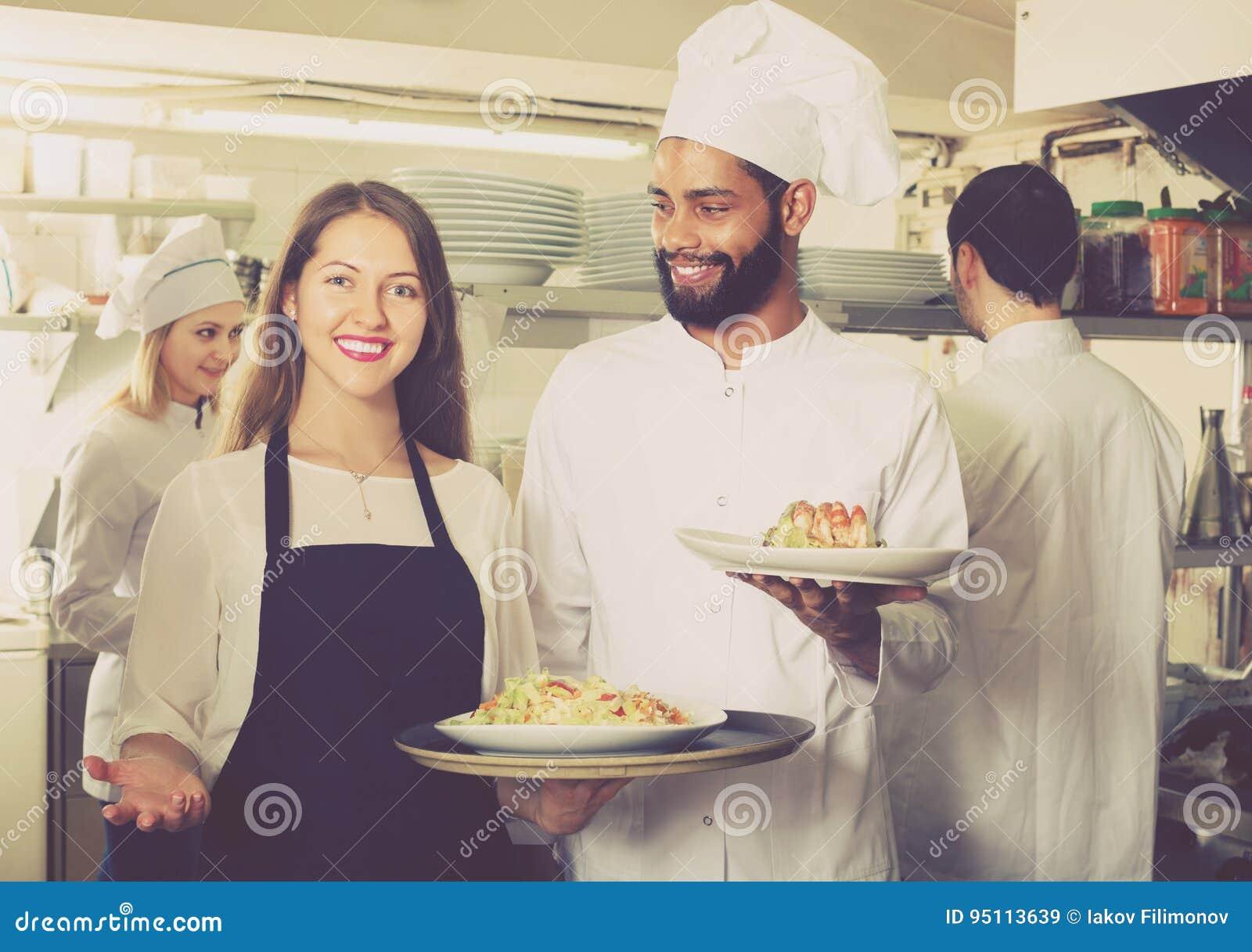 Empregada de mesa e equipe positivas do cozimento