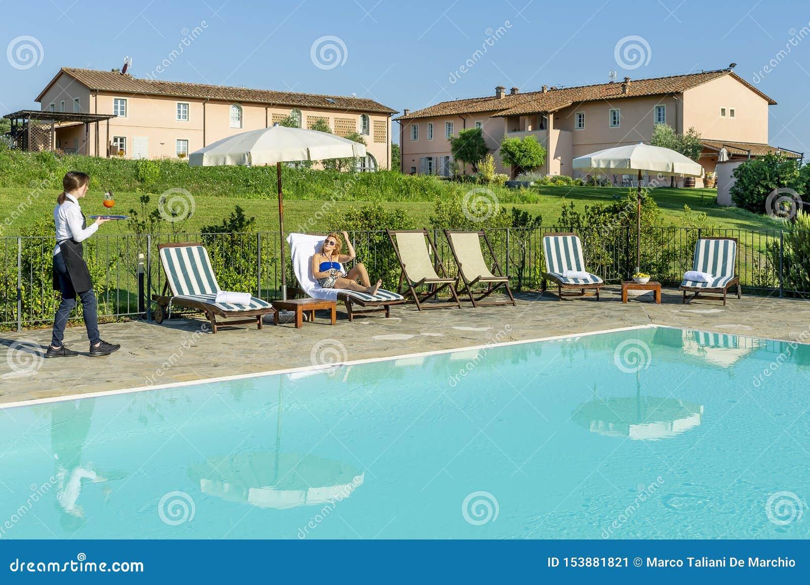 A empregada de mesa nova serve um cocktail da piscina a um cliente que senta-se em um vadio em um recurso no campo de Pisa, Itáli