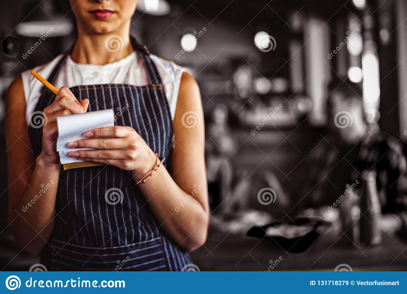 Empregada de mesa que toma a ordem no restaurante