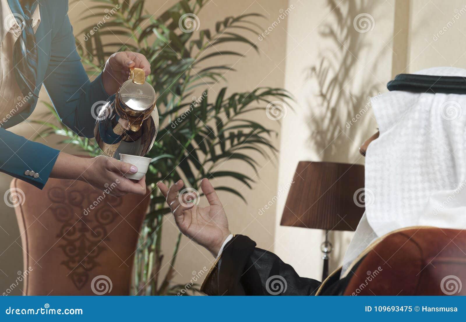 Empregada de mesa Serving Arabic Coffee a um homem árabe rico