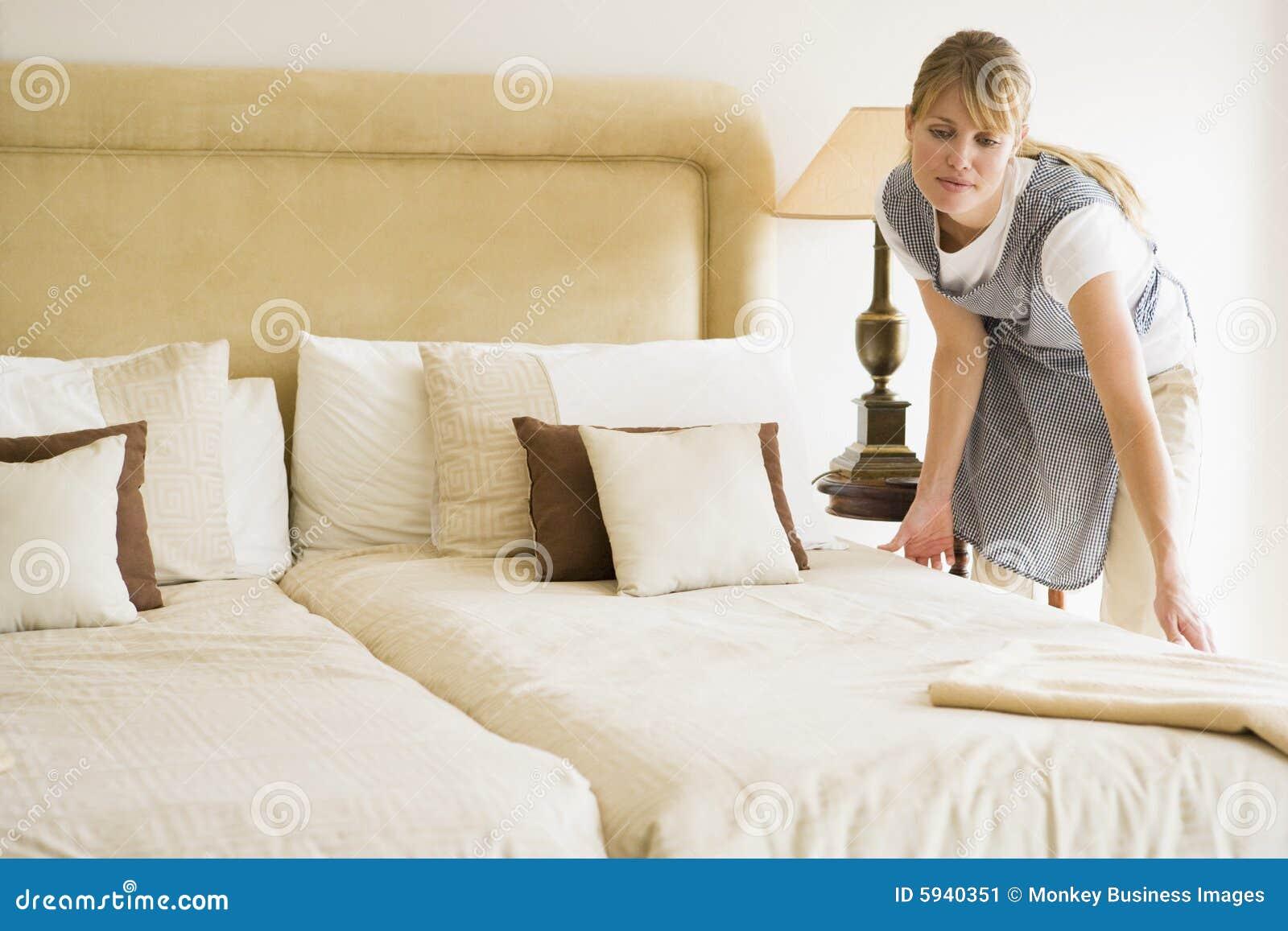 Empregada doméstica que faz a cama no quarto de hotel