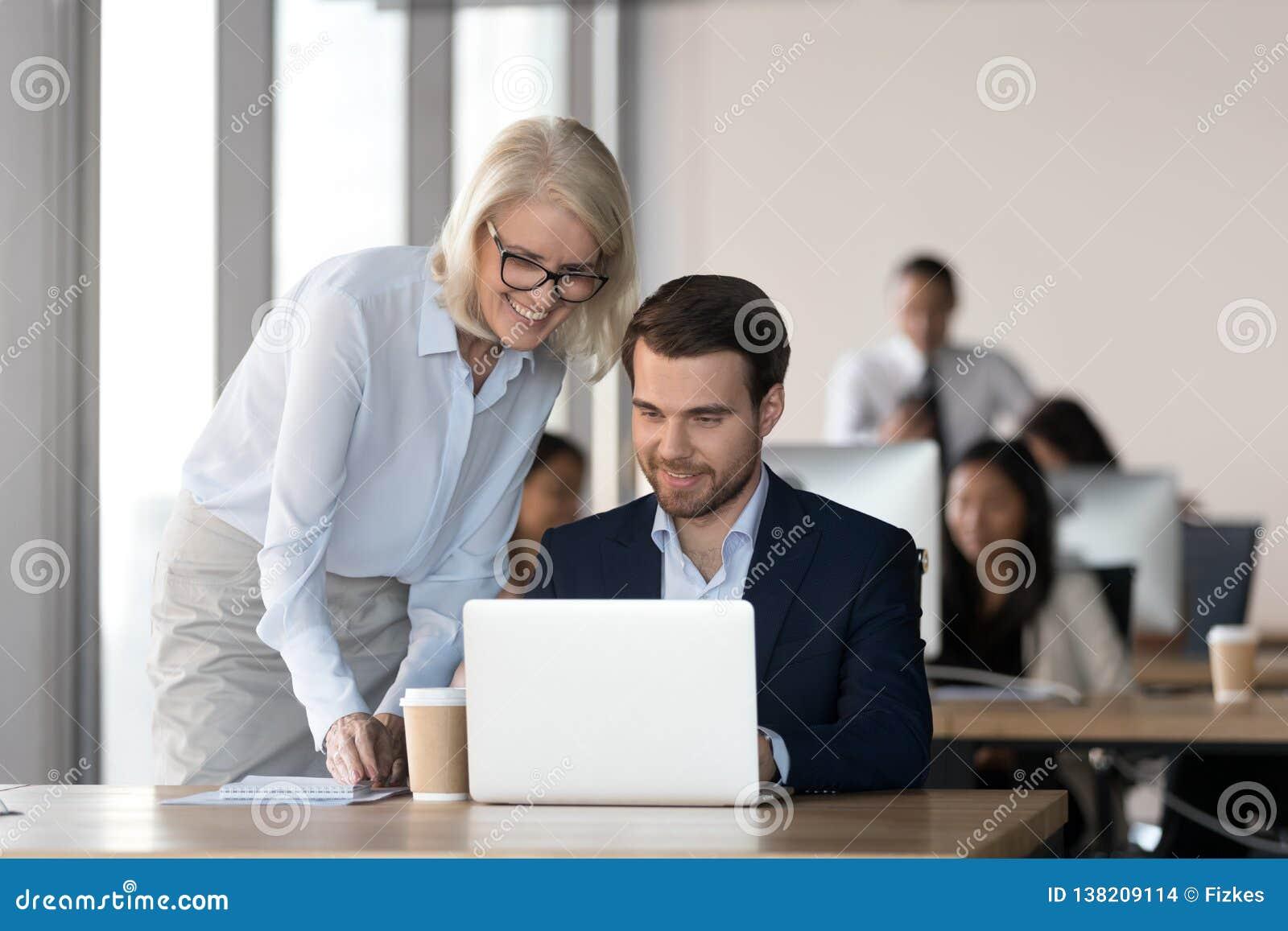 Empregado amigável do treinamento do mentor no escritório que ajuda com trabalho do computador