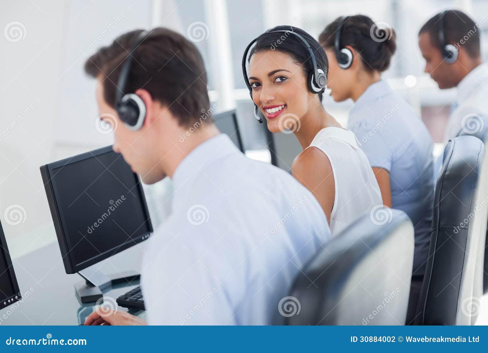 Empregado atrativo do centro de chamada que olha sobre o ombro