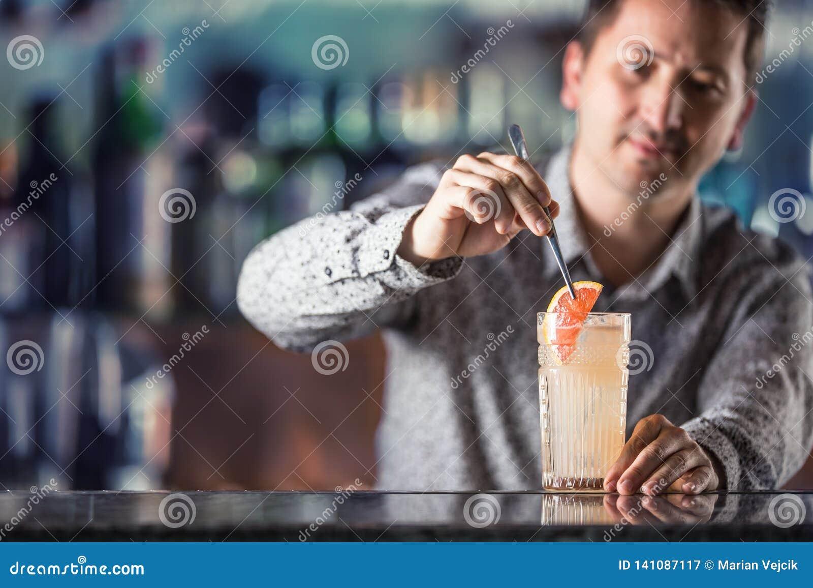 Empregado de bar profissional que faz a bebida alcoólica Paloma do cocktail