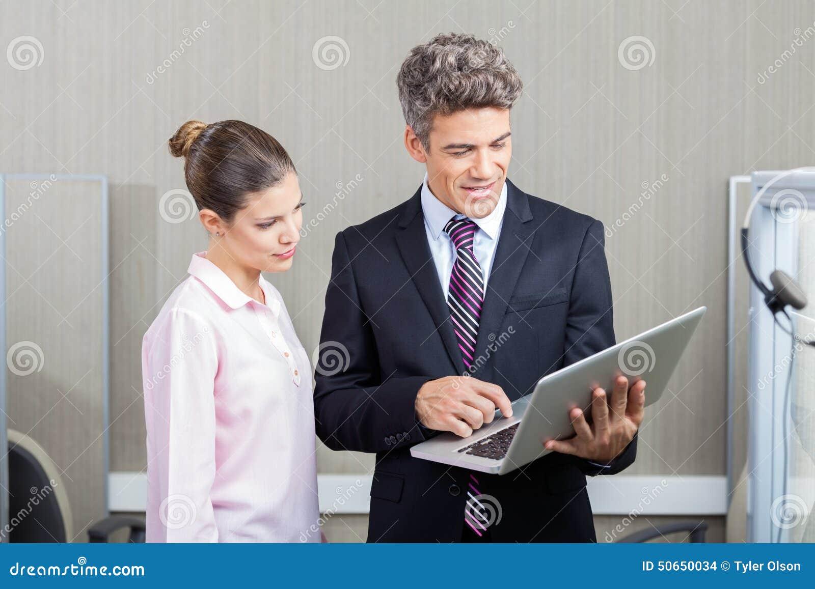 Empregado de And Call Center do homem de negócios que usa o portátil