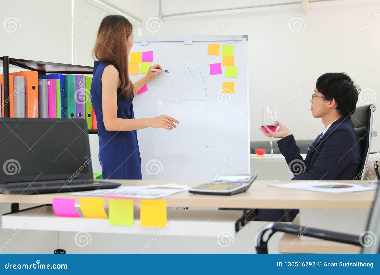 Empregado de escuta do chefe executivo asiático que explica estratégias na carta de aleta na sala de reuniões