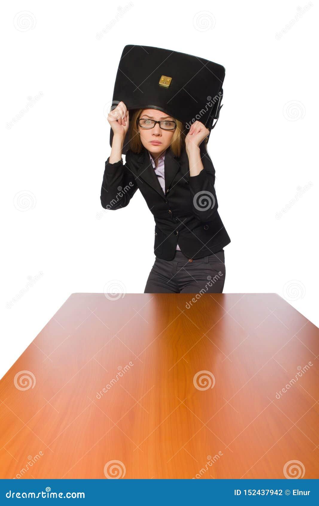Empregado do sexo feminino que senta-se na tabela longa isolada no branco