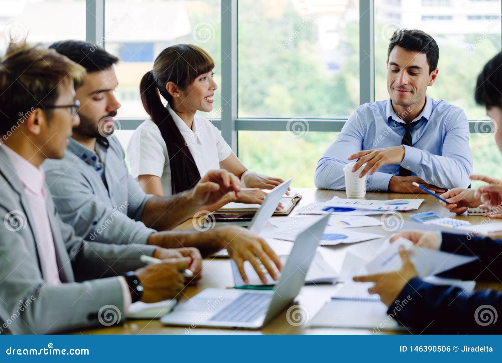 Empregados do sexo feminino e homens da empresa que encontram-se na sala de reunião que fala com uma cara de sorriso
