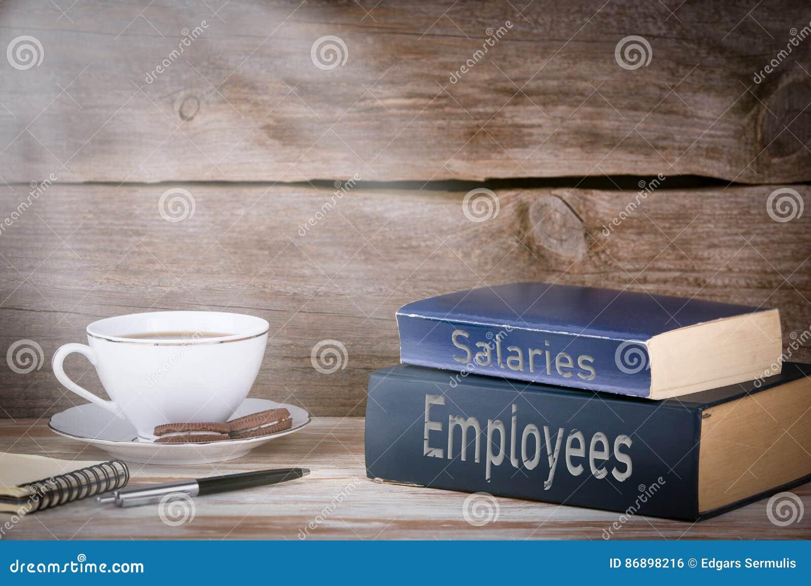 Empregados e salários Pilha de livros na mesa de madeira