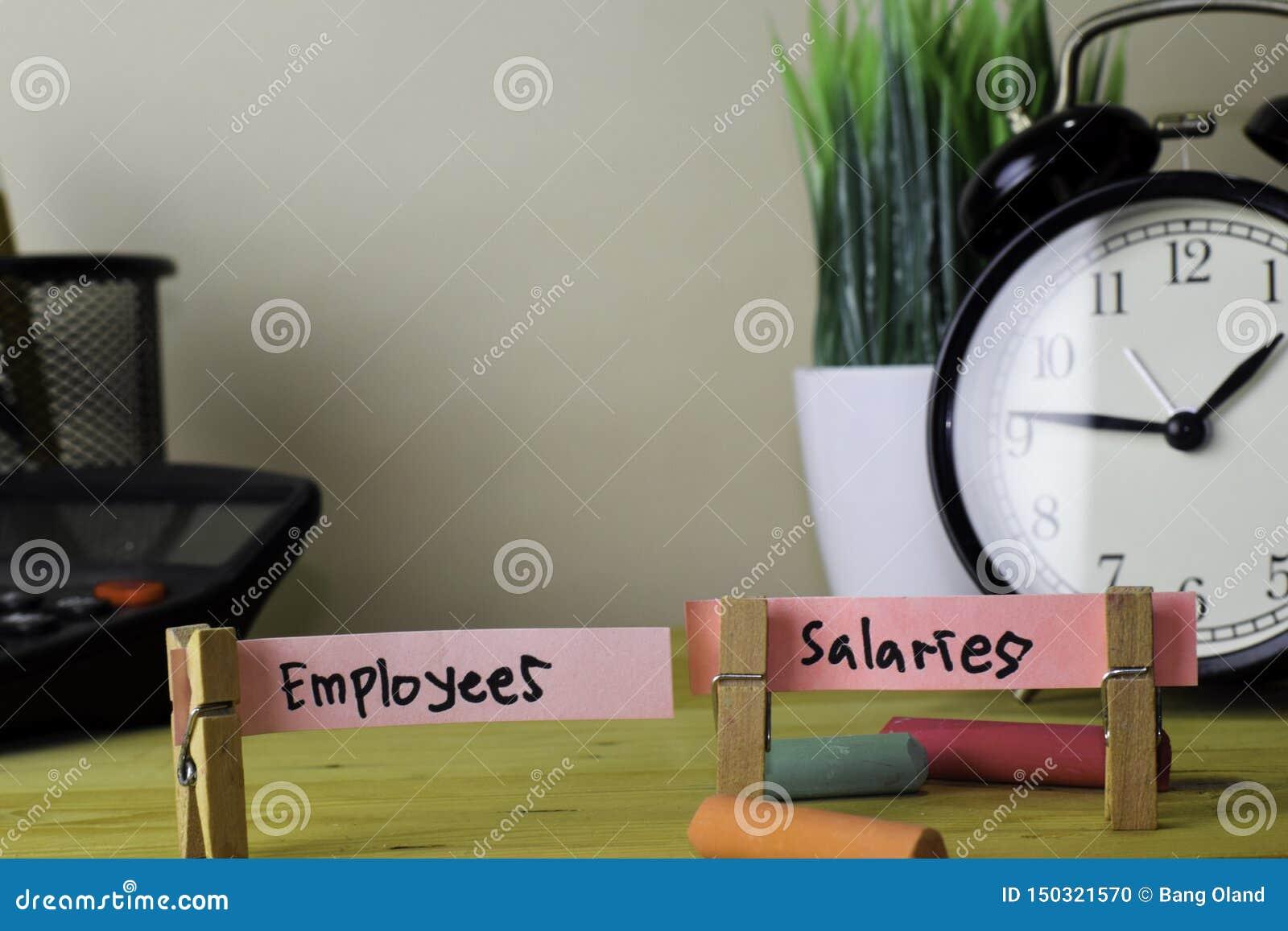 Empregados e sal?rios Escrita em notas pegajosas em Pegs de roupa na mesa de escritório de madeira